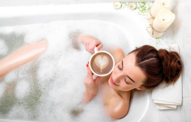 Young woman enjoying coffee while lying in the bath with foam and candles