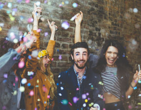 Group of four friends laughing out loud outdoor, sharing good and positive mood. Making party outdoor with champagne and confetti
