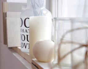 Kerzen und Vasen am Fensterbrett