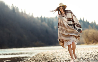 beautiful woman hipster walking on river beach in mountains, having fun and enjoying, boho travel concept, space for text