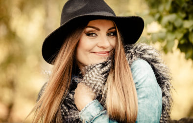 Fashion and style of female. Attractive and fashionable woman outdoor. Portrait of charming young lady hiding in fur waistcoat in park.