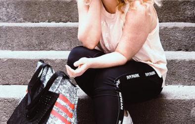 Bloggerin in Sportkleidung sitzt auf Treppe