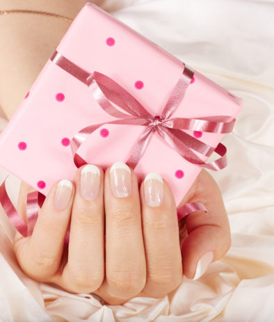 Hand with french manicured nails holding a gift box with bow