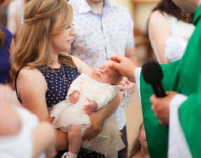Little cute girl on ceremony of child christening in church